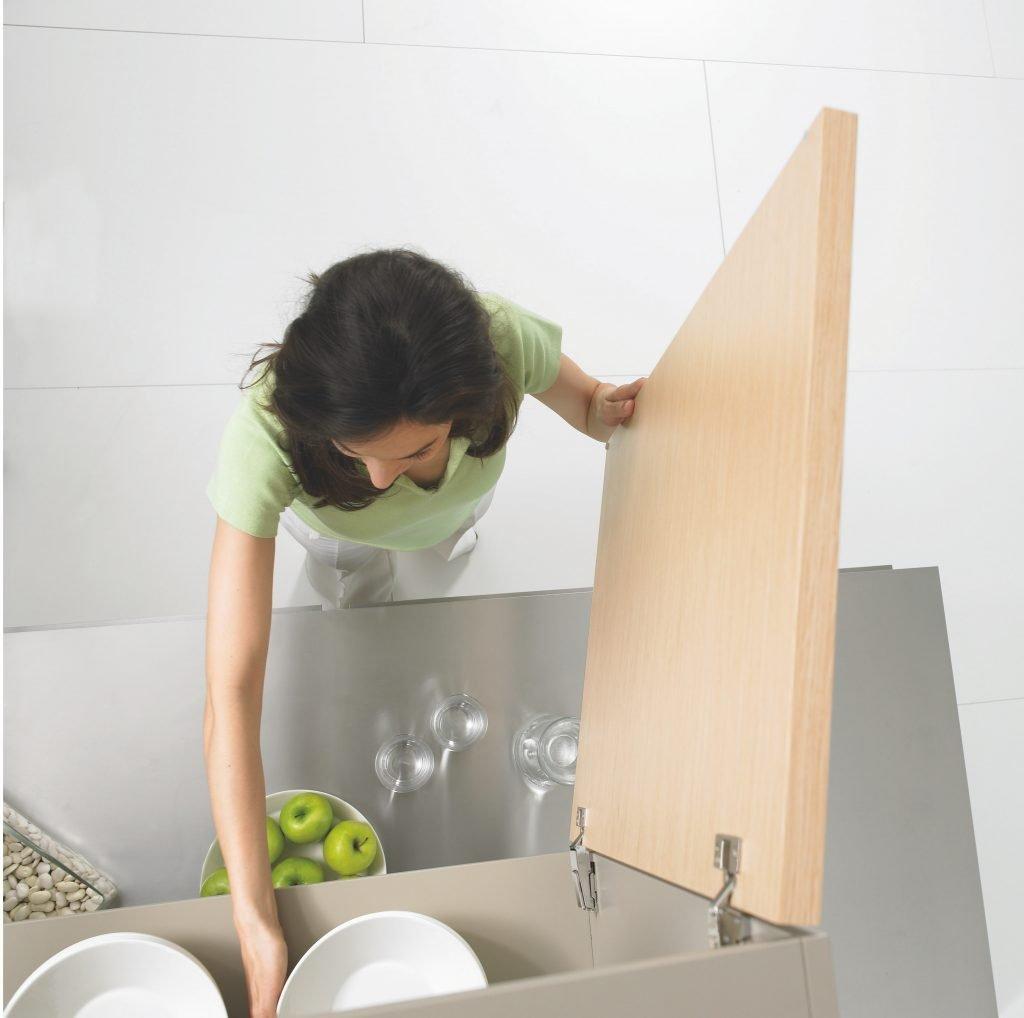 donna che sistema nel mobile della cucina
